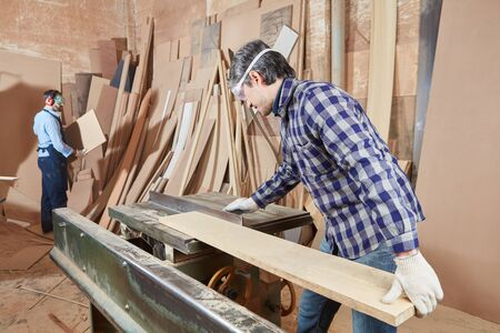 Carpenter working with circular saw in concentration Banque d'images