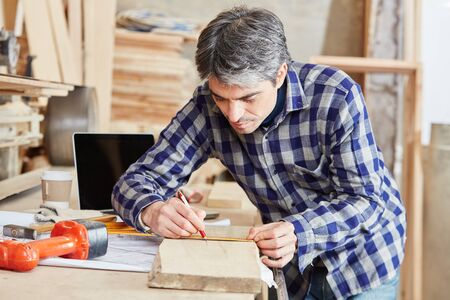 Carpenter measuring wood with accuracy at his shop