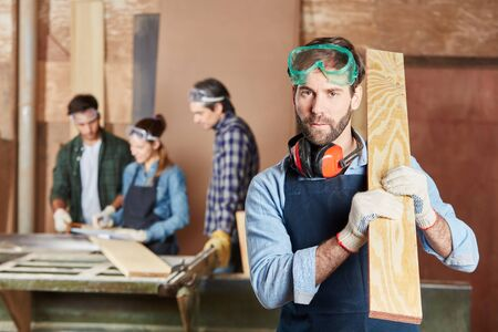 Carpenter with piece of wood at carpentry workshop Banque d'images
