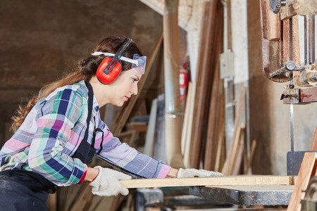 Woman during carpentry apprenticeship working with saw