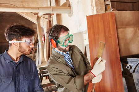 Carpenters cooperating and measuring wood at carpentry workshop