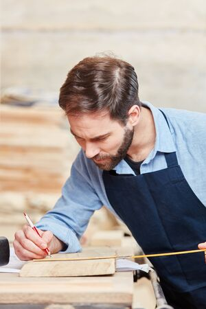 Carpenter measuring with concentration wood plate  Stock Photo