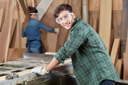 Man as carpenter working with protective googles