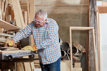 Senior citizen grinding wood with belt sander Banque d'images