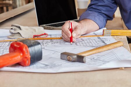 Construction plan and tools on workbench at carpentry shop