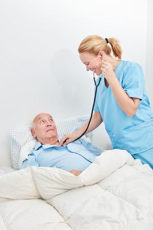 Nurse in nursing home or hospital examines a sick senior