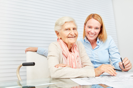 Smiling senior woman and young woman solve puzzles together as a memory workout