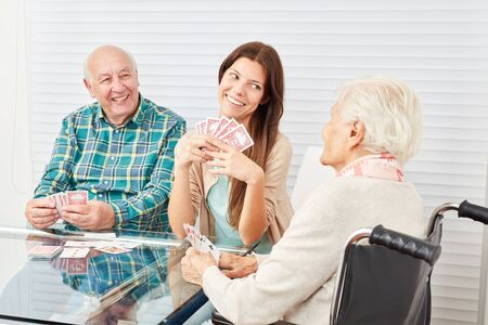 Happy couple seniors playing cards with granddaughter in retirement home Banque d'images