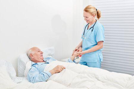 Nurse cares for bedridden senior in hospital or nursing home