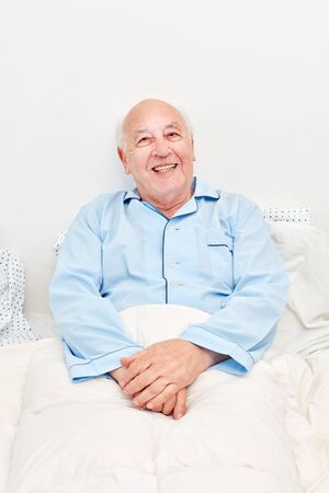 Senior man lies ill in bed in retirement home and smiles contentedly Banque d'images