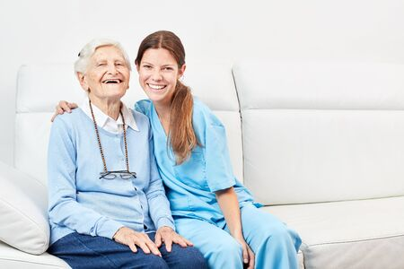 Smiling nursing assistant and laughing happy senior woman on the sofa
