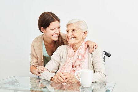 Caring care woman hugging a happy elderly woman on home visit Banque d'images