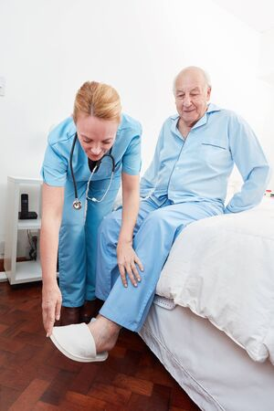 Nursing home nursing home helps a senior in putting on slippers