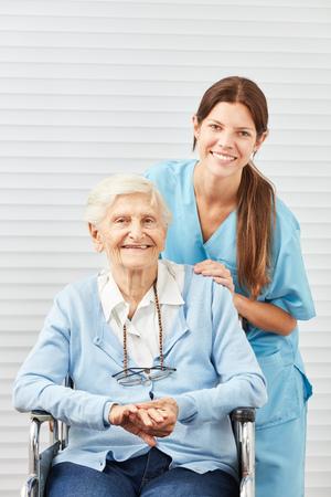 Young nursing woman or nurse and smiling senior citizen in wheelchair Stockfoto