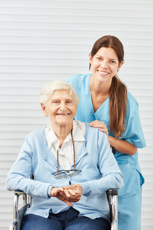 Young nursing woman or nurse and smiling senior citizen in wheelchair Фото со стока