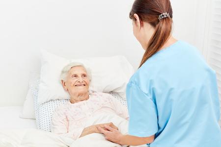 호스피스 또는 양로원에있는 노파가 간호사에게 위로 받고 있습니다. 스톡 콘텐츠