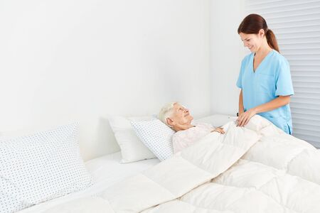 Female carer or geriatric nurse takes care of the elderly at the hospice