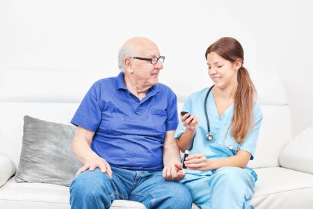 Nurse at the blood sugar measure with old man in the nursing home
