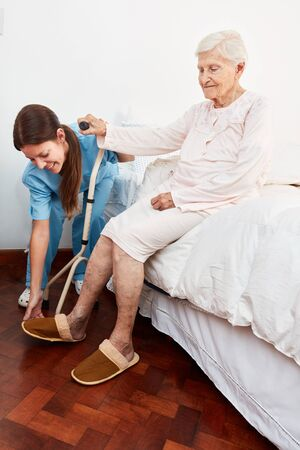 Disabled senior citizen gets help getting up from bed in nursing home