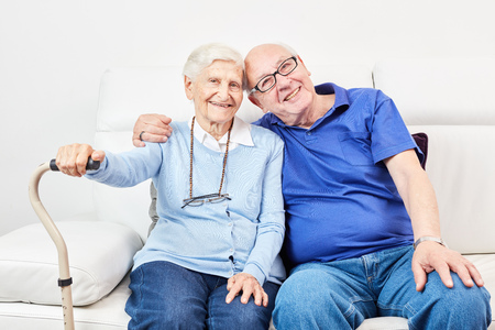 Old man and as old woman cuddle as happy couple on the sofa at home