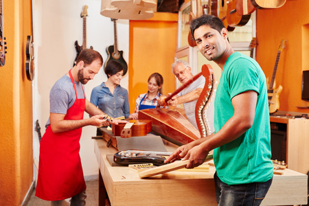 Young man as guitar maker's trainee in luthier's workshop