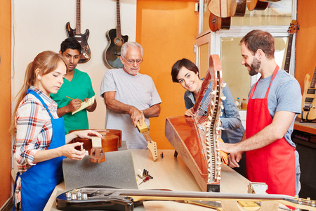 Luthier and apprentice team taking care of instruments in workshop
