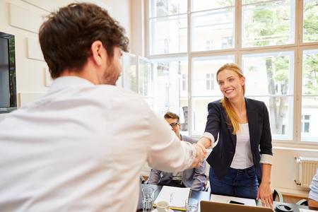 Frau, die Händedruck als Glückwunschgeste gibt Standard-Bild