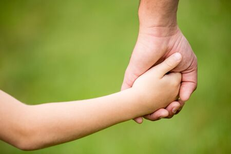 Hands of father and son holding them together as trust or family closeness