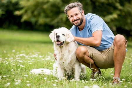 Man plays with his dog as friends together at garden in summer Stock Photo