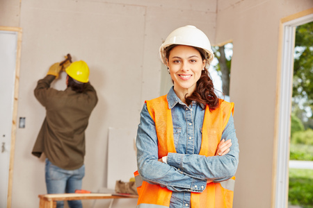 Young woman as apprentice of craftsman working at construction site