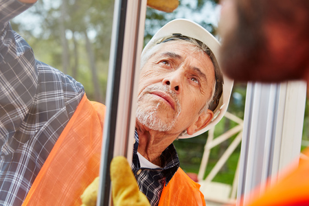 Senior competent window fitter assembles and modernizes new window Banque d'images - 94726135