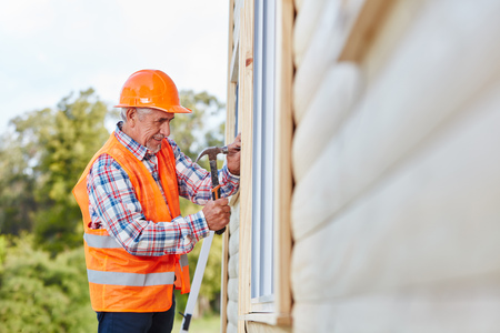 Old craftsman working on wood and hammering Stock Photo