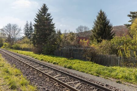 Rails for railway in the track beside garden in spring in germany Stock Photo