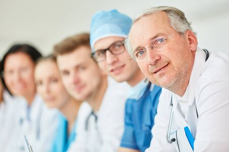 Senior doctor with experience next to team Stock Photo