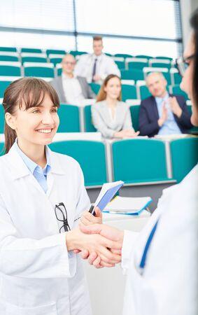 Medicine teacher congratulate student for passed exam in medical school