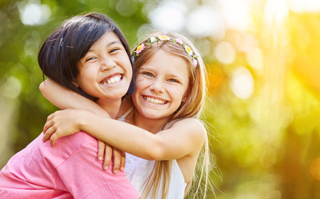 Asian and Caucasian girl hug each other laughing in the summer in the nature Stok Fotoğraf - 95922662