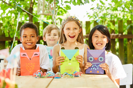 Multicultural group of kids with creative gift bags on kids birthday Stockfoto