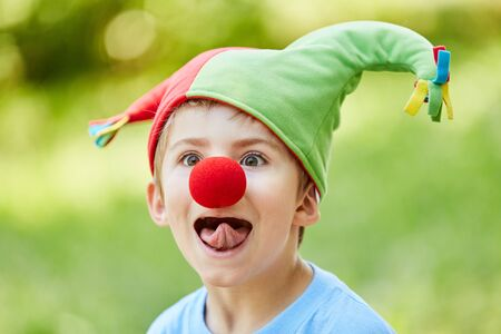 Boy with red nose and fools cap in the carnival sticks out his tongue