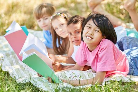 Group of elementary school kids do homework in the wild