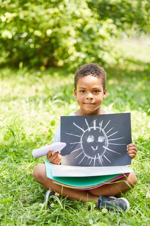 African boy proudly shows the chalk image of a sun in kindergarten