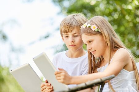 Two kids look curiously at tablet PC while chatting in social media