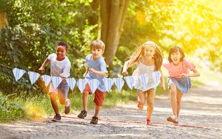 Grupa dzieciaków latem organizuje zawody wyścigowe w ogrodzie