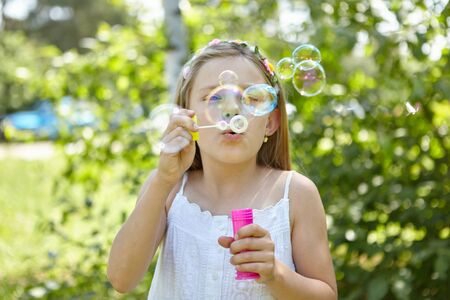 Girl blows soap bubbles in the summer as a sign of transience