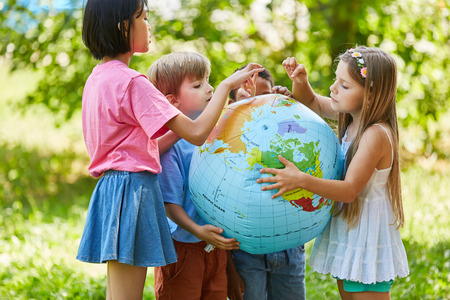 International children group together hold a world globe Foto de archivo