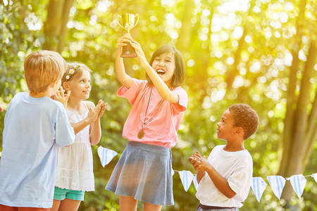 Asian girl with cup cheers as winner at award ceremony in summer
