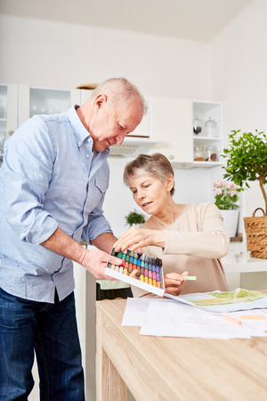 Senior man helps with creative painting woman suffering dementia