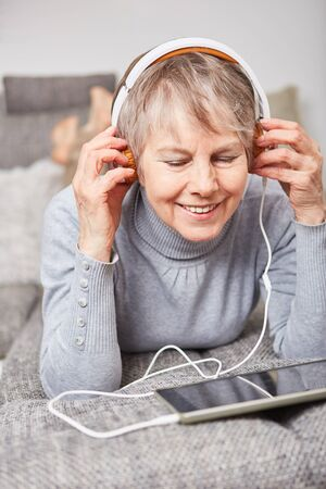 Senior woman streaming music with tablet