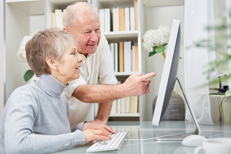 Senior citizens as couple learn about computer and online support