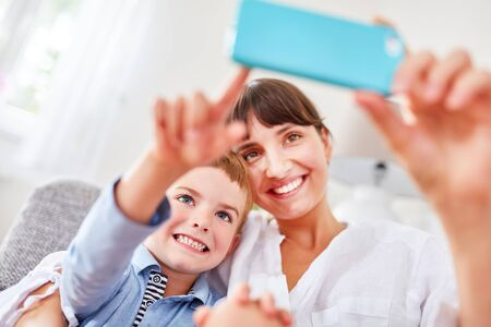 Happy boy and mother take a selfie with the camera cell phone 스톡 콘텐츠