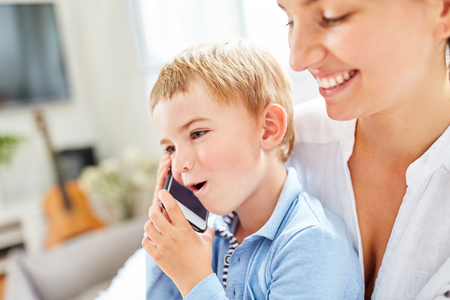 Smiling boy is phoning with smartphone under the supervision of the babysitter Stock Photo